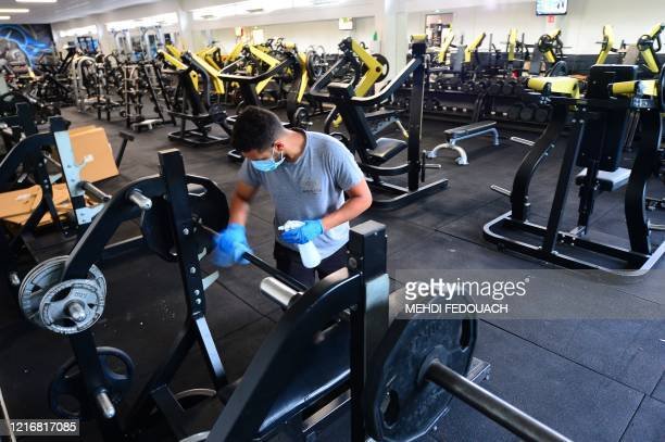 A worker disinfects a weight bench at the Body Staff Gym fitness centre on June 1 in ArtiguespresBordeaux southwestern France as part of safety...
