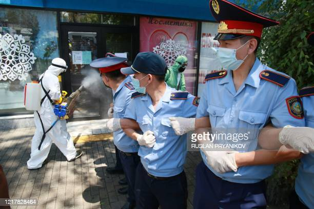 A worker disinfects a window as Kazakh police cordon a street on June 6 2020 in Almaty during a demonstration called by political opposition groups...