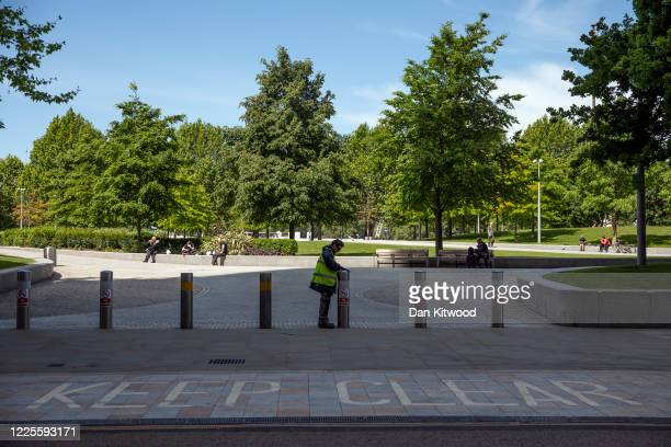 A worker disinfects bollards along the South Bank on May 18 2020 in London England The British government has started easing the lockdown it imposed...