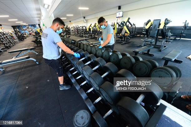 A worker disinfects dumbbells at the Body Staff Gym fitness centre on June 1 in ArtiguespresBordeaux southwestern France as part of safety measures...