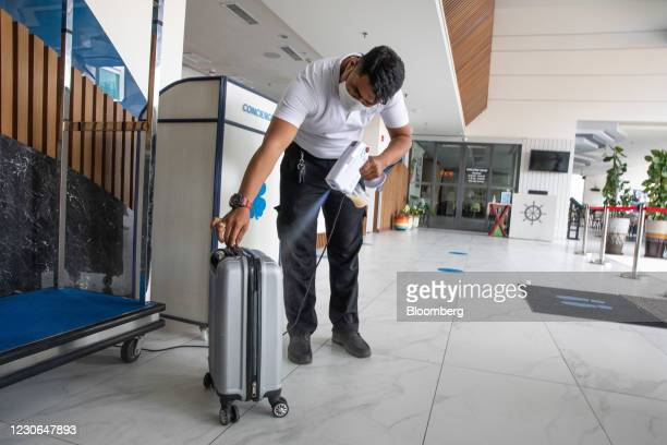 Worker disinfects luggage at Hotel Clover Patong Phuket in Patong, Phuket, Thailand, on Saturday, Dec. 19, 2020. The tepid response to Thailands...