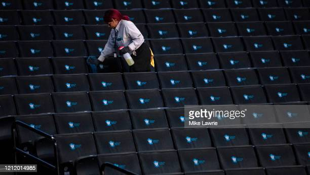 Worker disinfects seats prior to the start of the second round of the 2020 Atlantic 10 men's basketball tournament at Barclays Center on March 12,...