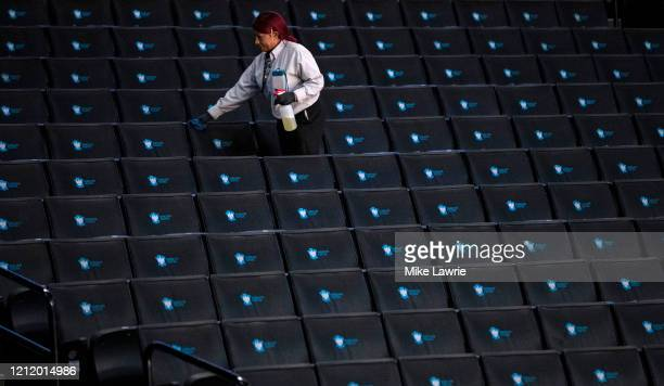 A worker disinfects seats prior to the start of the second round of the 2020 Atlantic 10 men's basketball tournament at Barclays Center on March 12...