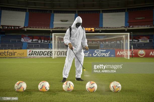 Worker disinfects the balls before the closed-door Copa Libertadores group phase football match between Colombia's Junior and Ecuador's Barcelona at...