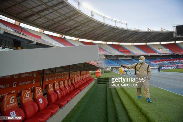 Worker disinfects the bench before the start of the closed-door Copa Libertadores group phase football match between Colombia's Junior and Ecuador's...