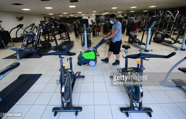A worker disinfects the floor of the Body Staff Gym fitness centre on June 1 in ArtiguespresBordeaux southwestern France as part of safety measures...