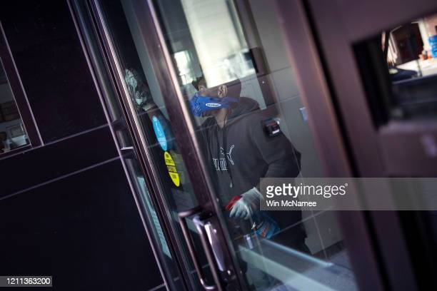 A worker disinfects the front doors of the School Without Walls High School which was closed today after a member of the school's staff reported...