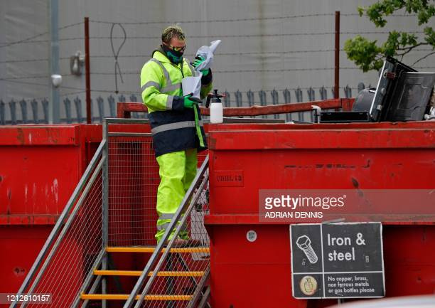 Worker disinfects the handrails to the staircase leading to the waste bins at the Aldershot Household Waste Recycling Centre in Aldershot, west of...