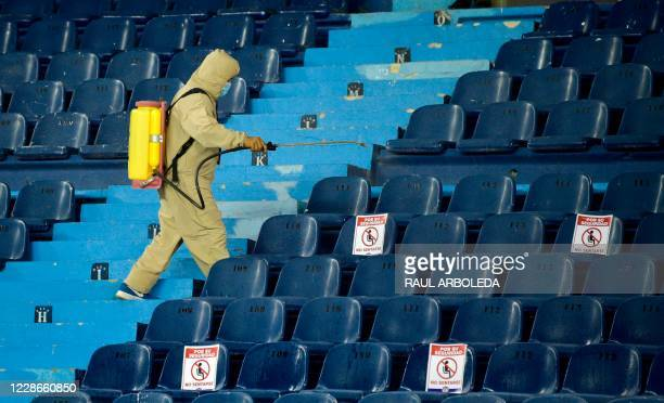 Worker disinfects the stands during the closed-door Copa Libertadores group phase football match between Colombia's Junior and Ecuador's...