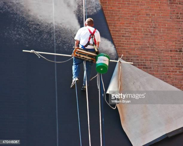 Worker dismantles a mural of LeBron James that hung on the side of the Sherwin Williams offices across from Quicken Loans Arena in downtown Cleveland.