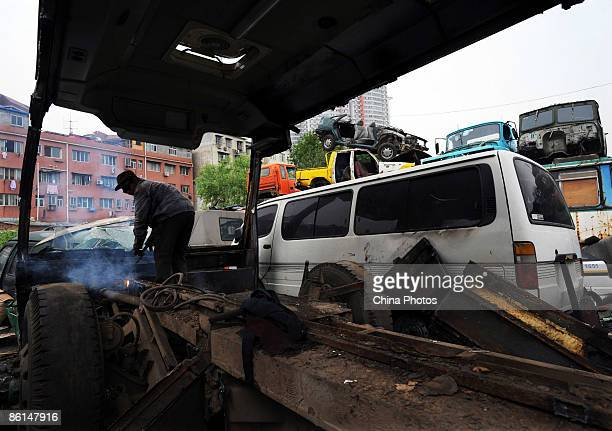 A worker dismantles a scrapped car at an auto scrapyard on April 21 2009 in Wuhan of Hubei Province China Official statistics showed that China's...