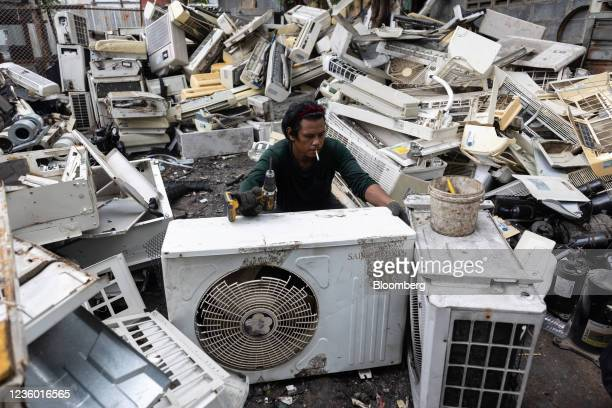 Worker dismantles an old air conditioner unit for parts at a recycling plant in Bangkok, Thailand, on Tuesday, Oct. 19, 2021. The Thai Cabinet on...