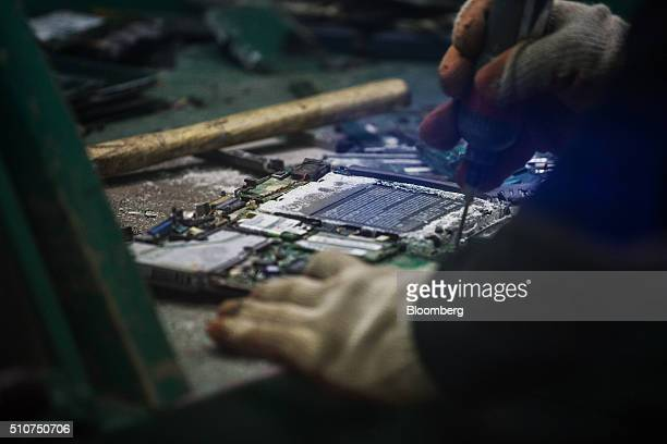 A worker dismantles computer parts at the Super Dragon Technology Inc ewaste processing facility in Taoyuan Taiwan on Wednesday Jan 13 2016 Super...