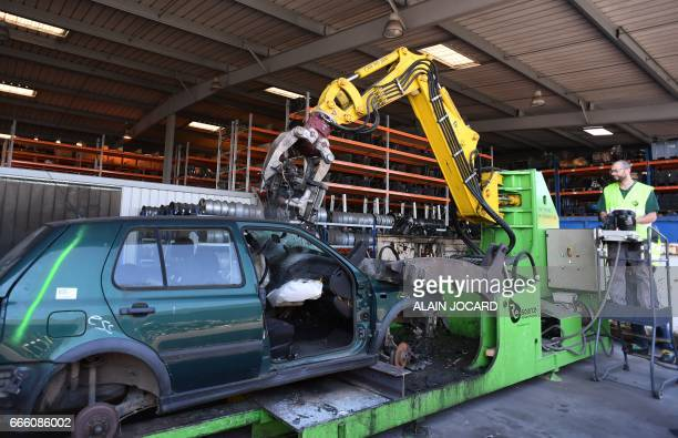 A worker dismantles parts of a car before recycling at the Indra Automobile Recycling centre in PruniersenSologne near Blois central France on April...