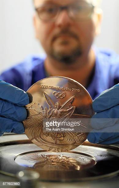 A worker displays a bronze medal for the Olympic games as the production in full swing on July 18 2016 in Rio de Janeiro Brazil