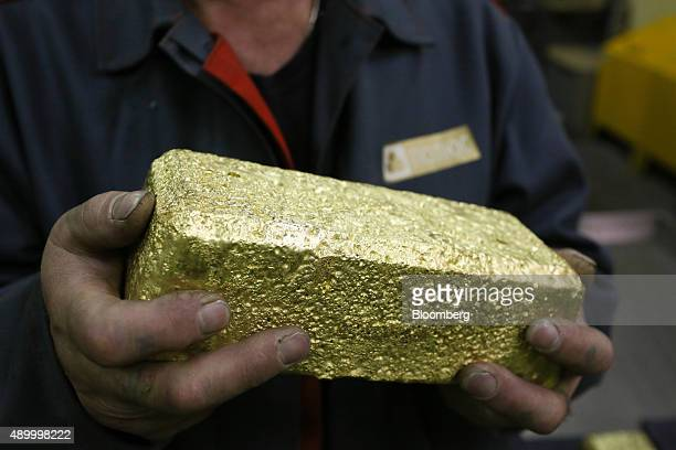 A worker displays a gold bar weighing 25 kilogrammes produced at the Verninsky GOK gold mine and processing plant operated by Polyus Gold...