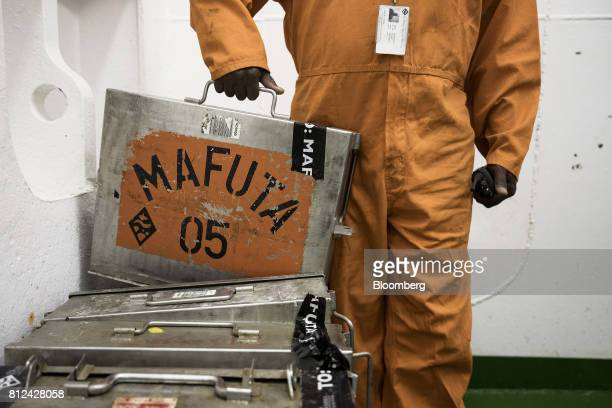 A worker displays a metal case used to transport sealed cans of diamonds from ship to shore aboard the Mafuta diamond mining vessel operated by...