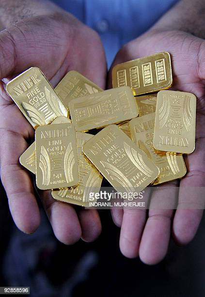 A worker displays gold bars at the National Indian Bullion Refinery 's gold and silver refinery in Mumbai on November 6 2009 The price of gold surged...