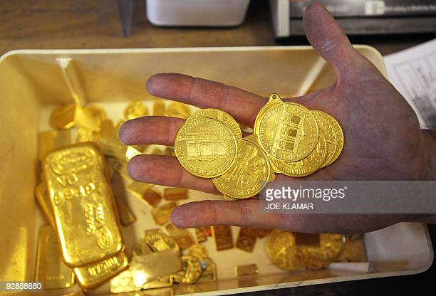 Worker displays scrap gold coins which are to be remelted as they didn't pass the standards at Austrian gold bullion factory Oegussa on October 8,...