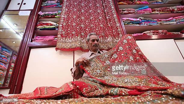 A worker displays wedding saris at Ram Chandra Krishan Chandra Trousseau shop in Chandni Chowk in New Delhi on Wednesday August 19 2009
