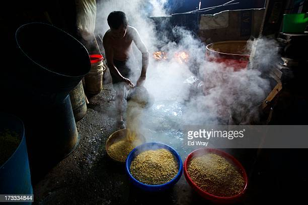 Worker drains soy beans after they have been boiled at a small tempeh factory on July 12, 2013 in Jakarta, Indonesia. Tempeh is an Indonesian staple...