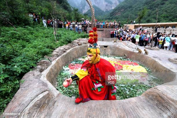 Worker dressed as the character Sun Wukong, also known as the Monkey King, from the Chinese classical novel 'Journey to the West', prepares fruit for...