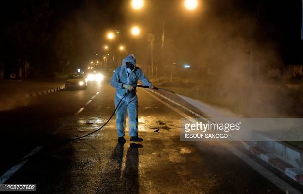 Worker dressed in full body gear disinfects streets in Abidjan on March 30 during a cleaning and disinfecting campaign, launched by Ivory Coast's...