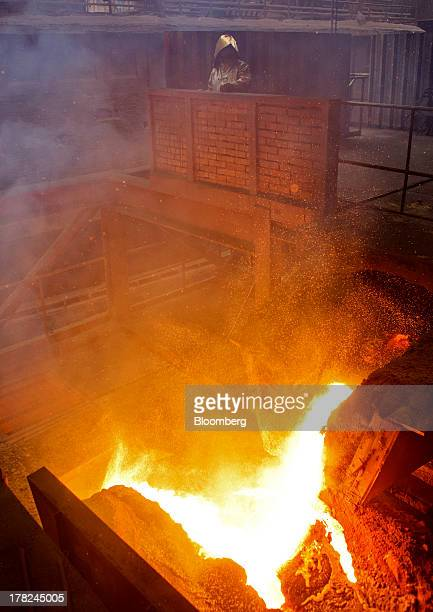 Worker dressed in heat retardant safety clothing monitors molten metal in the blast furnace at ArcelorMittal's steel plant in Ostrava, Czech...