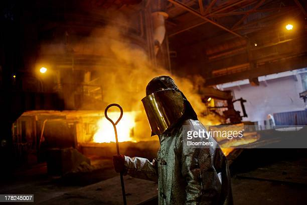 Worker dressed in heat retardant safety clothing pauses while working near the blast furnace at ArcelorMittal's steel plant in Ostrava, Czech...