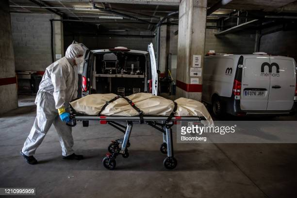 Image depicts death.) A worker dressed in personal protective equipment wheels a trolley containing the body of a victim of coronavirus into the...