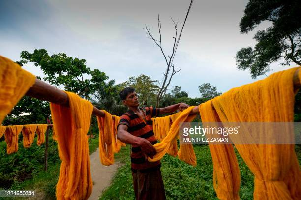 Worker dries fabric after dyeing them at a factory in Narsingdi, some 50 km from Dhaka, on July 4, 2020.
