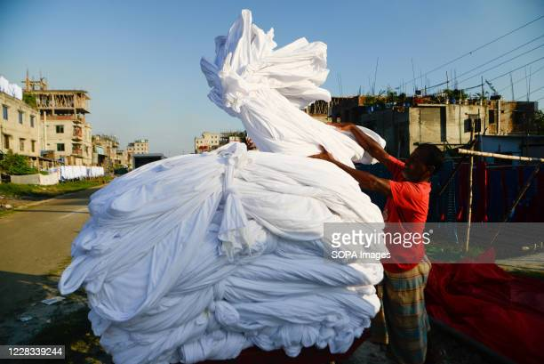 Worker dries fabric under the sun before dyeing them at a factory in Narayanganj. Most of the time workers dyeing clothes without wearing gloves and...