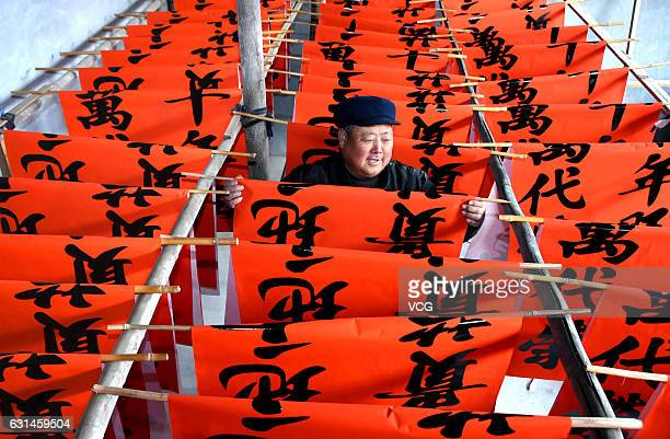A worker dries Spring Festival couplets at a factory on January 10 2017 in Zibo Shandong Province of China Plenty of traditional decorations are...