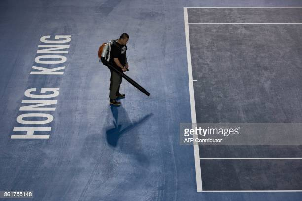 A worker dries the court after heavy rain from Typhoon Khanun which delayed the start of the women's singles final between Russia's Anastasia...