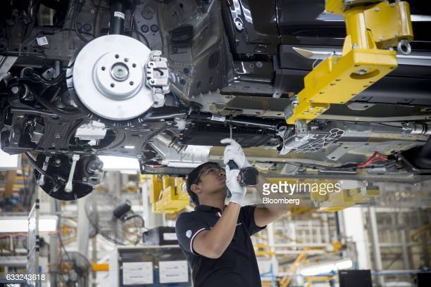 A worker drills a bolt in to a BMWX5 xDrive40e M Sport plugin hybrid vehicle at the BMW AG assembly plant in Amata Rayong province Thailand on...