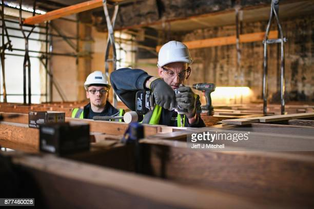 A worker drills as specialist carpenters from Lawrence McIntosh install the floor to the bookstore above the Mackintosh Library on November 22 2017...