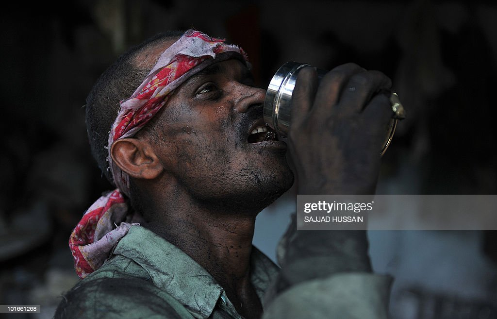 A worker drinks water at a local stainless steel manufacturing factory producing kitchenware goods in Mumbai on May 13, 2010. India is the tenth largest manufacturer of stainless steel in the world producing 18 to 20 lakh ton per annum. Mumbai is the biggest stainless steel trading centre in Asia for raw materials and finished products. AFP PHOTO/Sajjad HUSSAIN