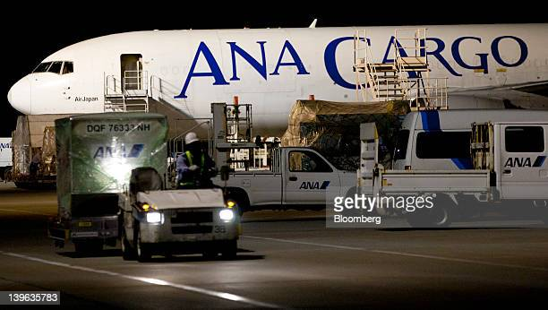 A worker drives a cart in front of an All Nippon Airways Co cargo aircraft parked at the company's cargo hub terminal at Naha Airport in Naha City...