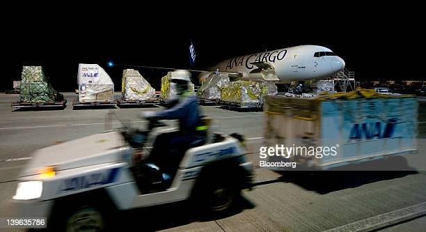 A worker drives a cart past an All Nippon Airways Co cargo aircraft parked at the company's cargo hub terminal at Naha Airport in Naha City Okinawa...