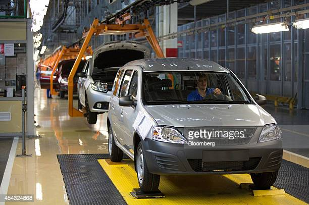 A worker drives a completed Lada Largus automobile off the assembly line at the OAO AvtoVAZ plant controlled by Renault SA and Nissan Motor Co in...