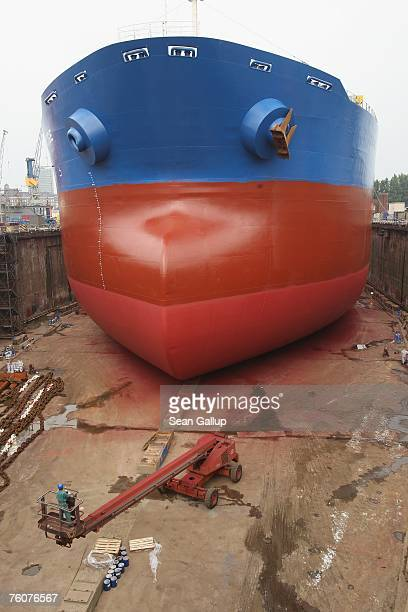 A worker drives a crane toward the hull of a ship undergoing maintenance and repairs at the Blohm Voss shipyard August 13 2007 in Hamburg Germany...