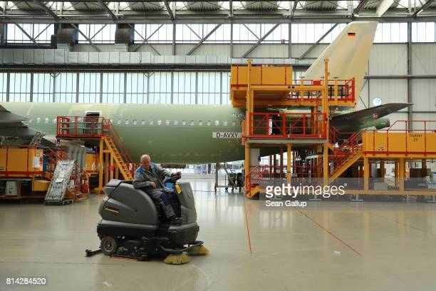 A worker drives a floor cleaning vehicle past a partiallyfinished passenger plane of the A320 series in an assembly hall at the Airbus factory on...