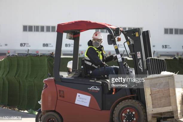 A worker drives a fork lift outside the Tesla Inc Gigafactory in Shanghai China on Monday Feb 17 2020 Tesla has fully resumed deliveries of its...