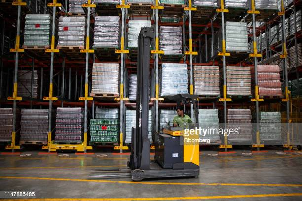 A worker drives a forklift past CocaCola Co brand drinks inside a warehouse at the CocaCola Cambodia Bottling Plant operated by Cambodia Beverage Co...