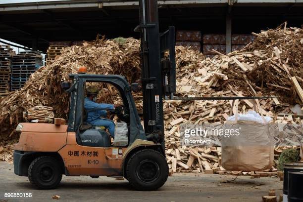 A worker drives a forklift past piles of scrap wood at the Gonoike Biomass Power Station operated by Gonoike Bioenergy Corp a subsidiary of...