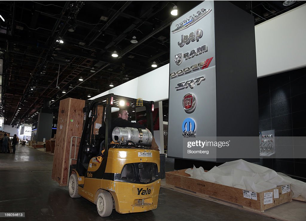 A worker drives a forklift past the Chrysler Group LLC exhibit during an advance tour of the North American International Auto Show (NAIAS) at Cobo Hall in Detroit, Michigan, U.S., on Thursday, Jan. 10, 2013. More than 23,000 attendees representing almost 2,000 companies are expected to attend the industry preview for NAIAS on Jan. 16-17. The general public can attend the show from Jan. 19-27. Photographer: Jeff Kowalsky/Bloomberg via Getty Images