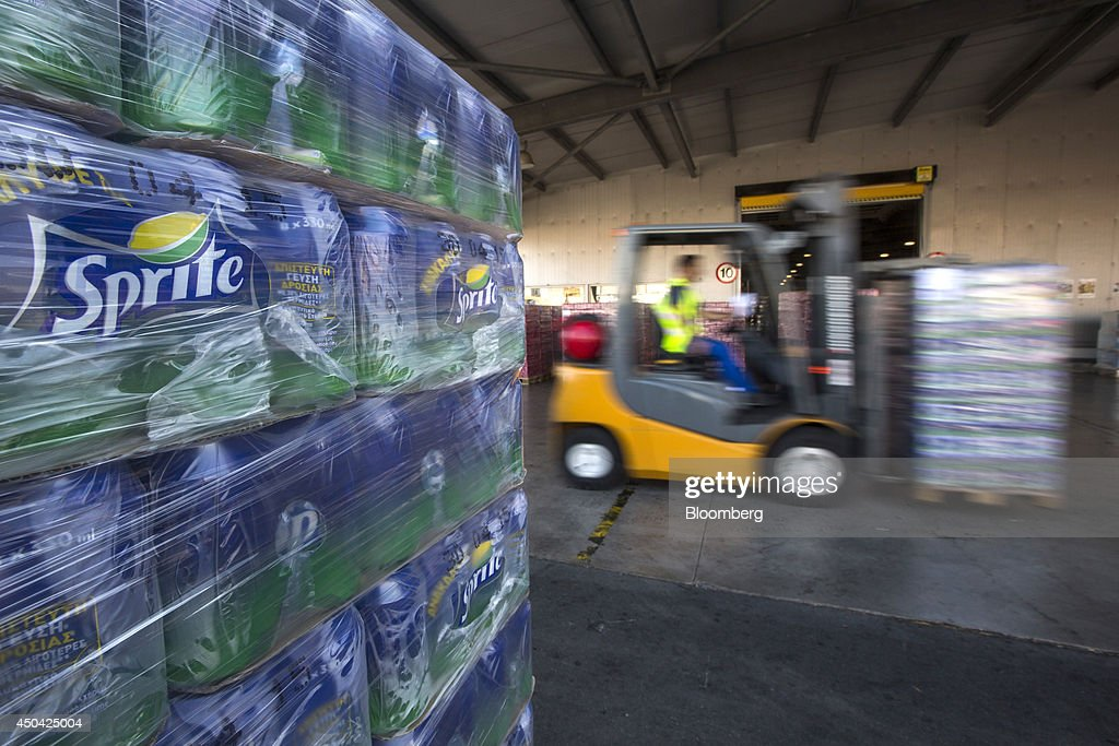 A worker drives a fork-lift truck past a pallet of Sprite beverage cans in the loading bay at the Lanitis Bros Ltd. bottling plant, part of the Coca-Cola Hellenic Group, in Nicosia, Cyprus, on Tuesday, June 10, 2014. Zug, Switzerland-based Coca-Cola Hellenic Bottling Co., which distributes Coca-Cola products in countries including Russia, wants to move away from using imported sugar for its Russian operations by 2015. Photographer: Andrew Caballero-Reynolds/Bloomberg via Getty Images