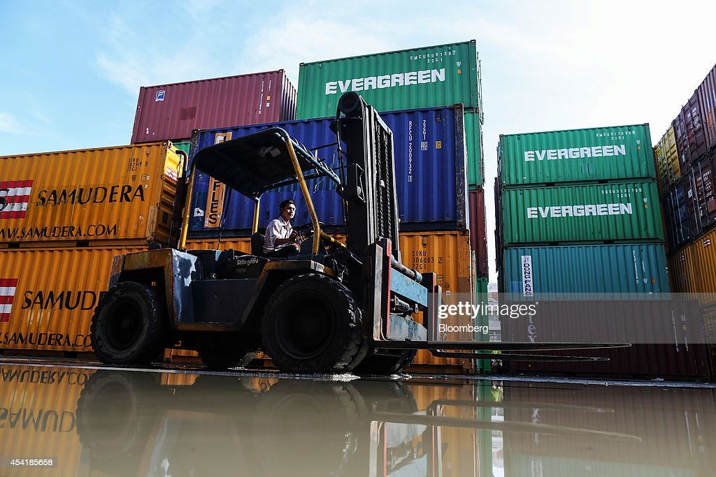 A worker drives a forklift truck past stacked containers at the Custom Global Service Co. container depot in Bangkok, Thailand, on Monday, Aug. 25, 2014. Thailand's trade figures are scheduled for release on Aug. 27. Photographer: Dario Pignatelli/Bloomberg via Getty Images