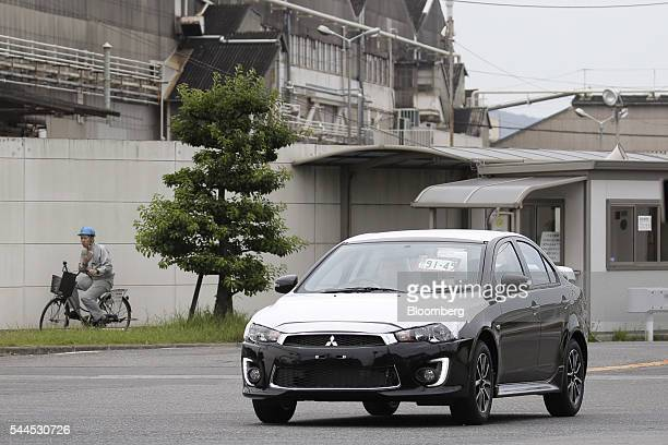 A worker drives a Mitsubishi Motors Corp vehicle near the company's Mizushima plant in Kurashiki Okayama Prefecture Japan on Friday June 17 2016...