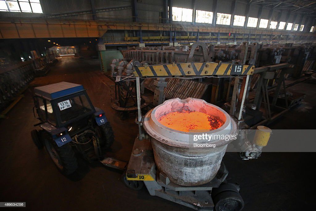 A worker drives a tractor pulling a crucible filled with molten aluminum past electrolysis baths inside the electrolysis shop at the Irkutsk aluminium smelter, operated by United Co. Rusal, in Shelekhov, Russia, on Monday, Sept. 21, 2015. The biggest aluminum producers are discussing the introduction of a 'green' trademark for the lightweight metal that could be sold at a premium and encourage carbon footprint reductions among rivals, United Co. Rusal's deputy chief executive officer said. Photographer: Andrey Rudakov/Bloomberg via Getty Images